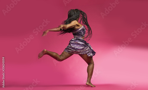 Poster Dance School Beautiful African Black girl wearing traditional colorful African outfit does a dramatic dance move against a colorful pink background