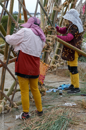 Fotografie, Obraz  Two villagers are working on a project where they are weaving material into bamboo frames