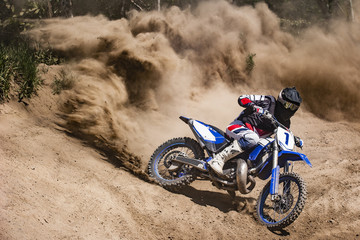 Fototapeta Motocross rider creates a large cloud of dust and debris