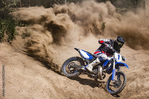 Foto op Plexiglas Motorsport Motocross rider creates a large cloud of dust and debris