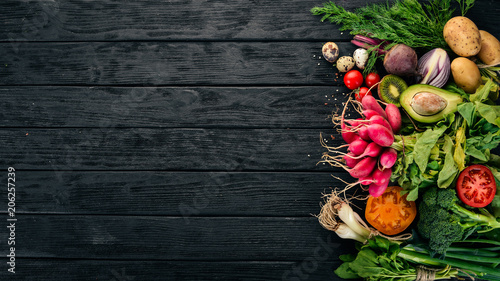 Poster Cuisine Healthy food. Vegetables and fruits. On a black wooden background. Top view. Copy space.