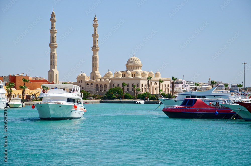 Fototapeta Seascape with motor yachts in marina. View of mosque  in the  background. Hurghada, Egypt