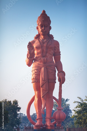 The view on a huge statue of red Hanuman with the raised hand in blessing gesture.