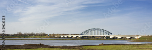 Fotografía  Typical Dutch river IJssel landscape with blue sky, white clouds, wind and sunny