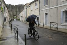 Radfahrer Mit Regenschirm In Aigues-Mortes (Südfrankreich)