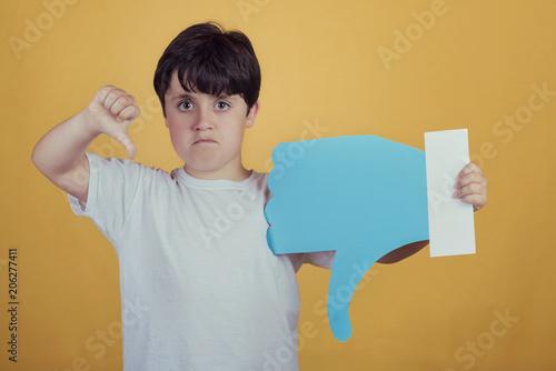 niño con un dislike grande sobre fondo amarillo Canvas-taulu