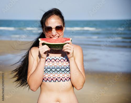 Fotobehang Wintersporten Woman eating watermelon on the beach