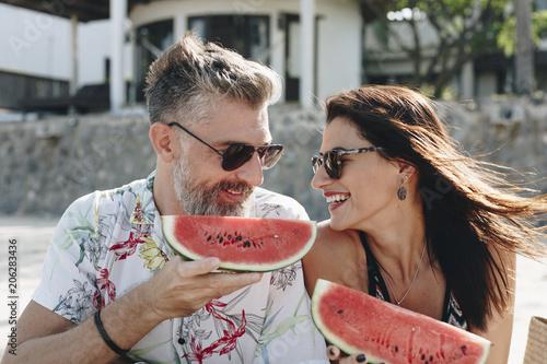 Fotobehang Wintersporten Couple eating watermelon at the beach