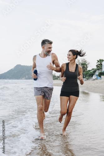 Fotobehang Wintersporten Couple jogging on a beach