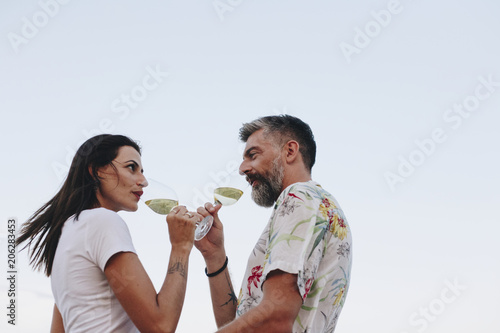 Fotobehang Wintersporten Couple enjoying a glass of wine by the beach