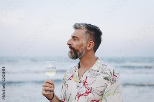 Fotobehang Wintersporten Man drinking a glass of wine by the beach