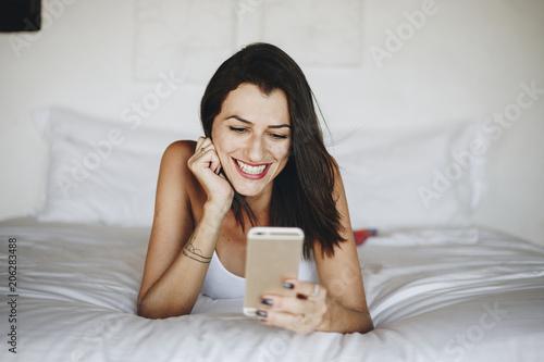 Fotobehang Wintersporten Woman using a mobile phone in bed