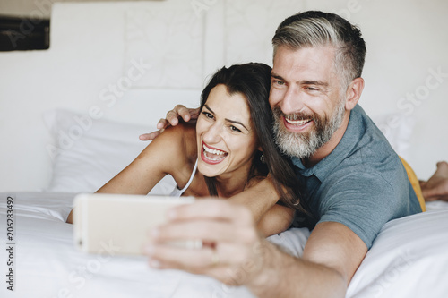 Fotobehang Wintersporten Honeymooners taking a selfie in bed