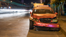 Crashed Car Stands On A Road In The City Center. Damaged Taxi In The Night City.