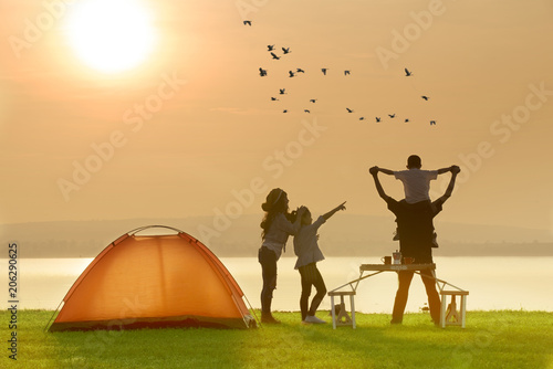 Poster Camping Happy family camping near the lake with sunset or sunrise background,happy family concept