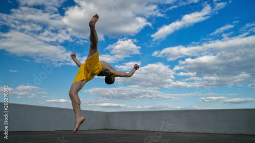 Foto op Aluminium Vechtsport Tricking on street. Martial arts. Man flips back barefoot. Shooted from bottom foreshortening against sky.
