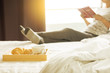 Woman reading book or newspaper and drinking coffee breakfast on bed during the morning