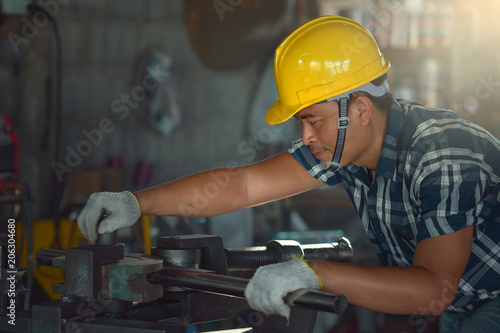 Foto  Young Asian worker in a metal cutting machine factory.