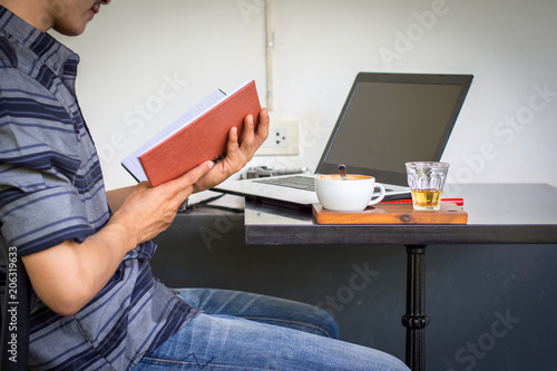 Young Man Is Reading A Book With A Laptop On The Table Kaufen Sie