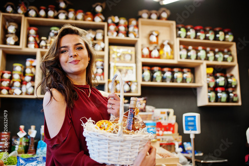Fotografie, Obraz  Girl in red holding different products on basket at deli store.