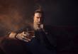 canvas print picture - Mann mit Bart sitzt auf dem Couch, trinkt Whiskey und raucht eine Zigarre