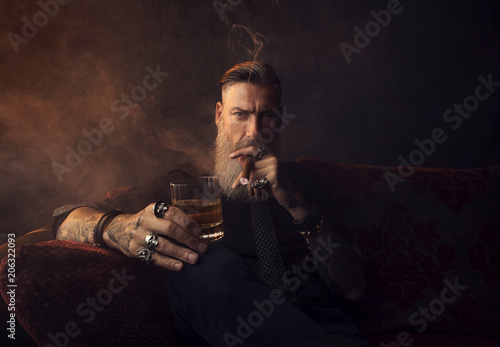 Mann mit Bart sitzt auf dem Couch, trinkt Whiskey und raucht eine Zigarre Fototapeta
