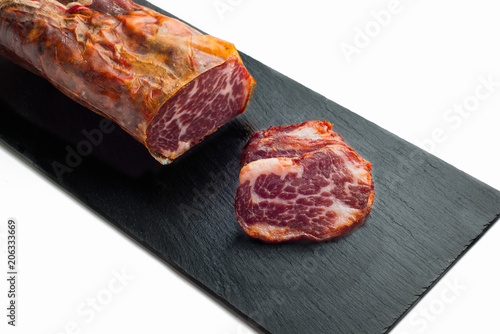 Photo black tray of delicious Iberian pork loin on white background