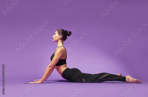 Fototapeta Long haired beautiful pilates or yoga athlete does a graceful pose while wearing a tight sports outfit against a bright purple background in a studio obraz