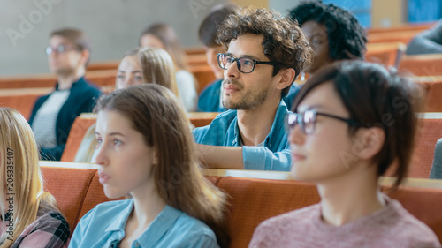 Handsome and Smart Hispanic Man Listens to a Lecture in a Classroom Full of Multi Ethnic Students. Shallow Depth of Field.