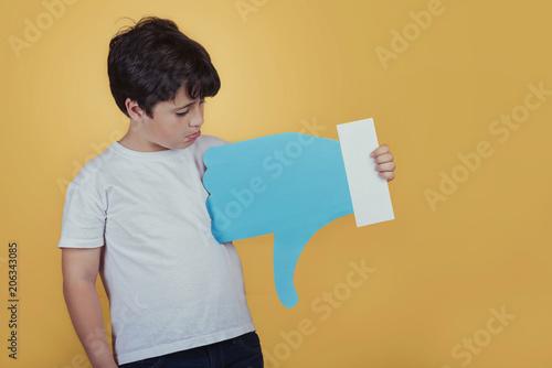 Fotografering  niño triste con un dislike grande sobre fondo amarillo
