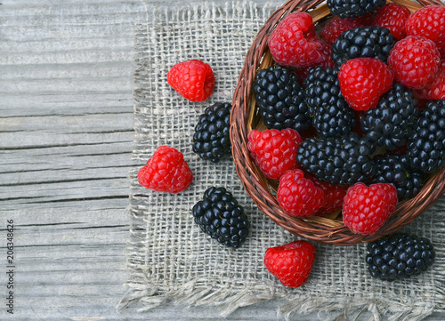 Freshly picked organic blackberries and raspberries in a basket on old wooden table.Healthy eating,vegan food or diet concept.Selective focus.
