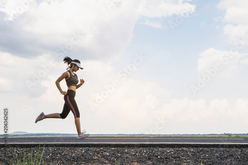 Foto  Young fitness woman runner athlete running at road