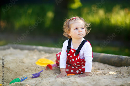 Fotografie, Obraz  Cute toddler girl playing in sand on outdoor playground