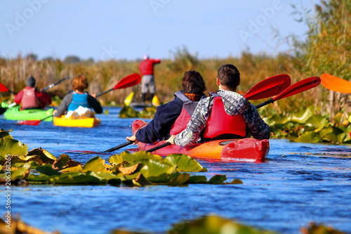 Kayakers row on the river among water lilies on a sunny autumn day Wallpaper Mural