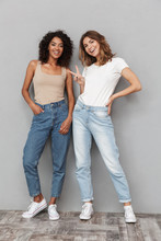 Full Length Portrait Of Two Cheerful Young Women