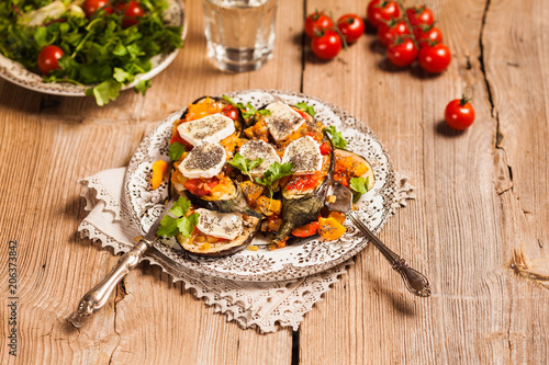 Baked eggplant with yellow and red bell pepper, tomatoes, garlic, goat cheese and chia seeds in plate on an old wooden rustic table