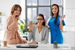 business and people concept - group of businesswomen waving hands at office