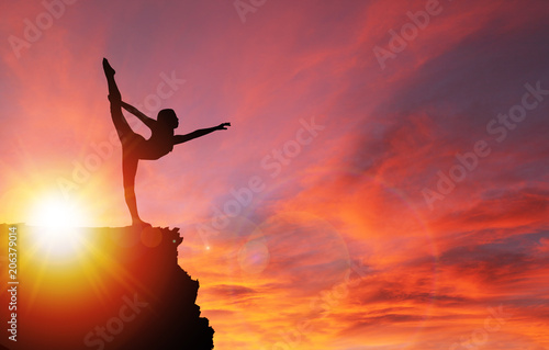 Photo sur Toile Rouge Silhouette of Girl Exercising on Edge of Cliff at Sunrise