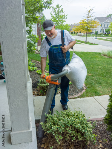 Fotografie, Obraz  Man vacuuming leaves at the entrance to his house