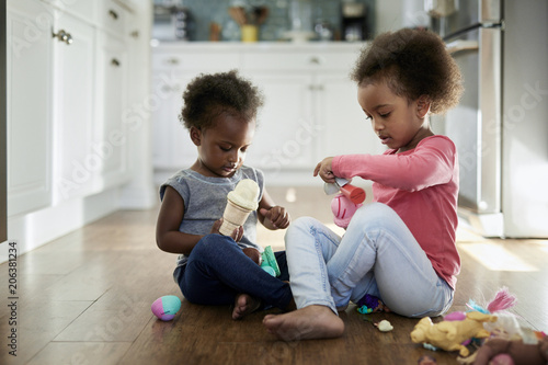 Sisters playing with ice cream toys while sitting on hardwood floor at home