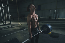 Shirtless Male Athlete Lifting...