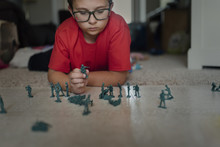 Boy Playing With Miniature Pla...