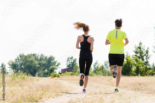 Couple jogging in nature rear view