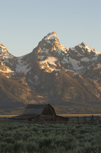 Barn On Grassy Field Against Snow Covered Mountain At Grand Teton National Park During Sunset