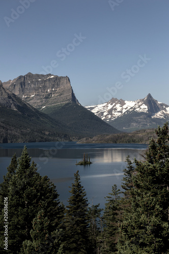 Poster Bergen Scenic view of lake by mountains against clear blue sky at Glacier National Park