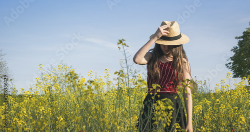 Teenage girl wearing hat while standing on field against blue sky during sunny day
