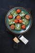 Turquoise plate with spinach ravioli, fried cherry tomatoes and grated parmesan, flatlay on a black stone background, vertical shot
