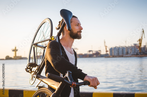 Fotobehang Fiets Stylish handsome man walking with bicycle on his shoulder during sunset or sunrise with sea port on background