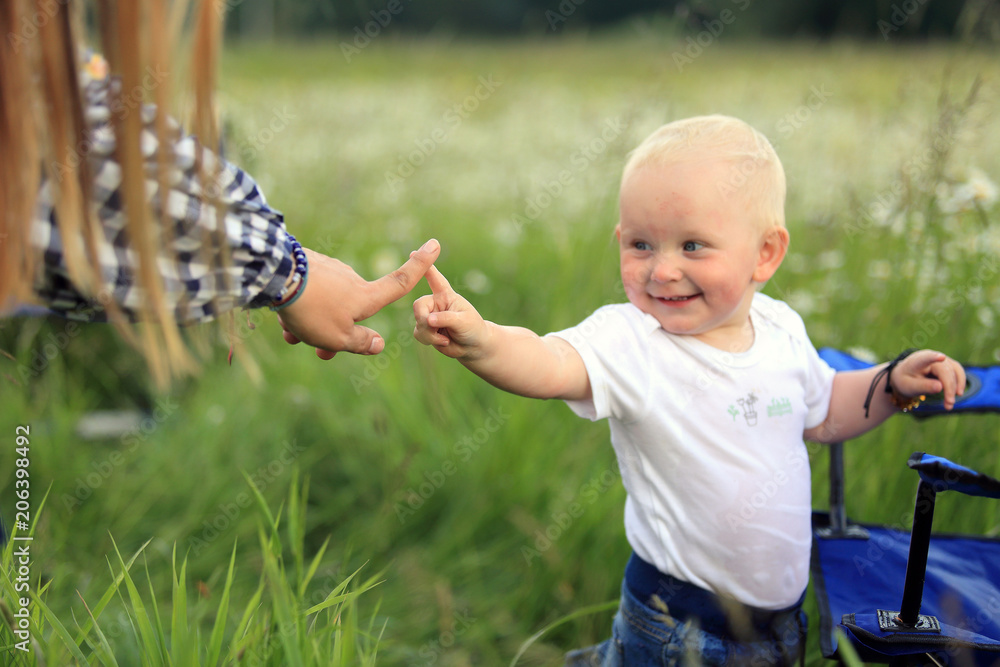 Fototapeta Mała dziewczynka bawi się z matką na łące.