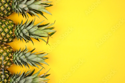 Pineapple fruit side border on a bright yellow background. Top view, flat lay with copy space.